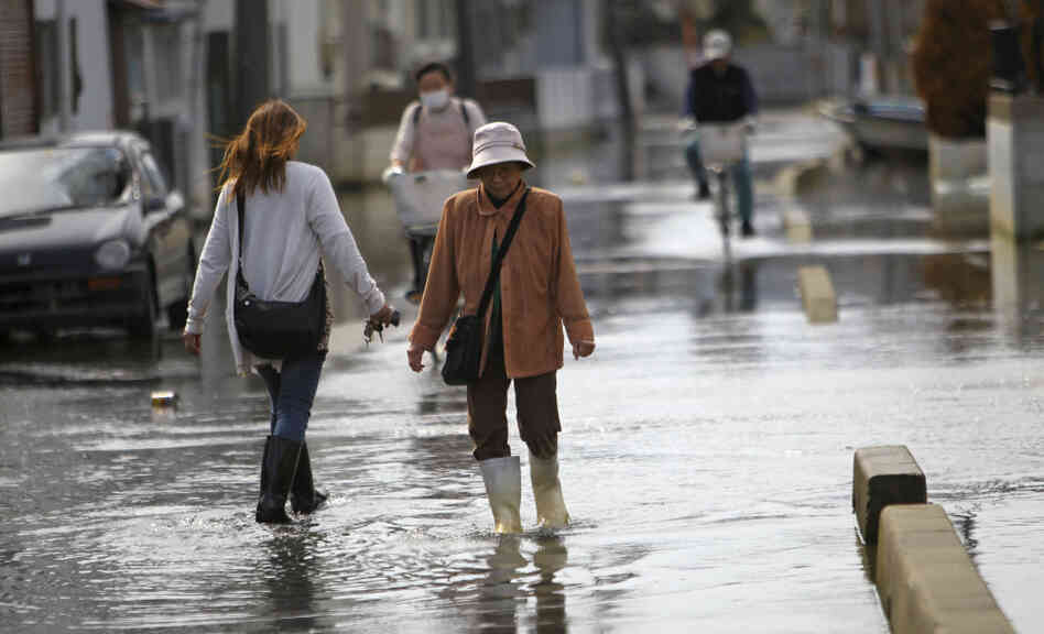 Residents stroll in a flooded street in Ishinomaki, M