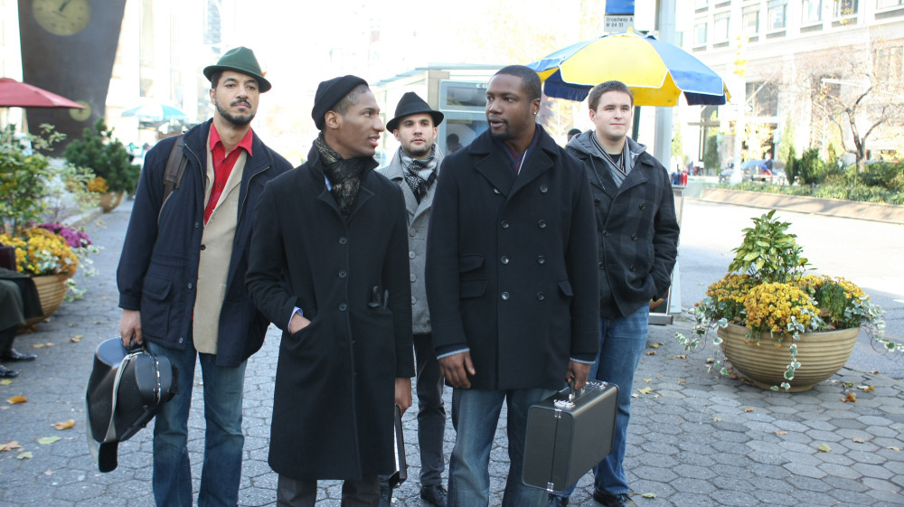 Delmond Lambreaux (Rob Brown, front right) speaks with his band members in New York, including pianist Jonathan Batiste as himself (front left).