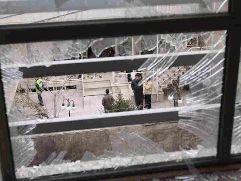 Iranian security agents are seen through a shattered window after Iranian nuclear engineer Massoud Ali Mohammadi was killed outside his Tehran residence when a booby-trapped motorcycle exploded on Jan. 12, 2010.