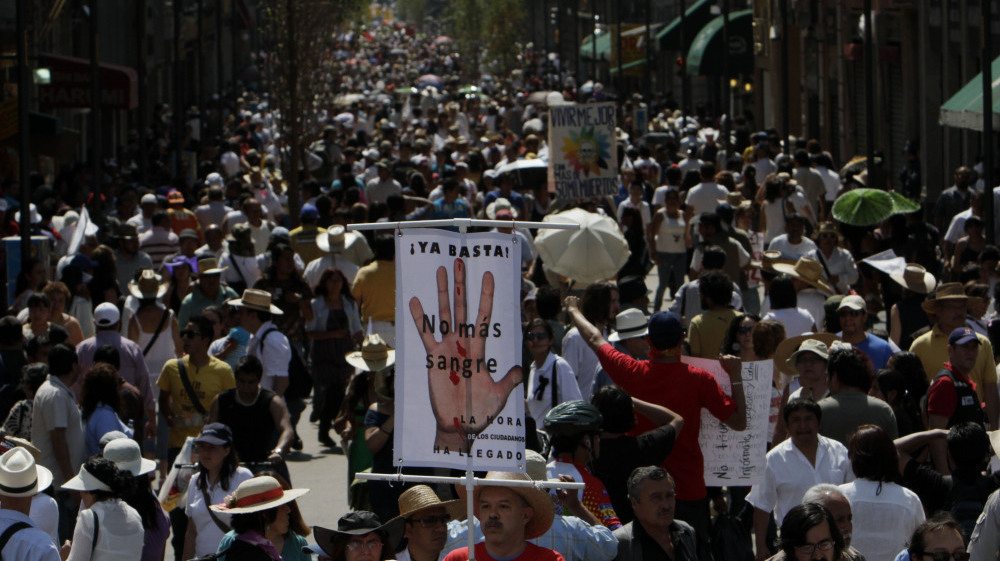 A demonstrator holds a sign reading 'Stop! no more Blood', during a march against gang violence in Mexico City, Sunday, May 8, 2011.