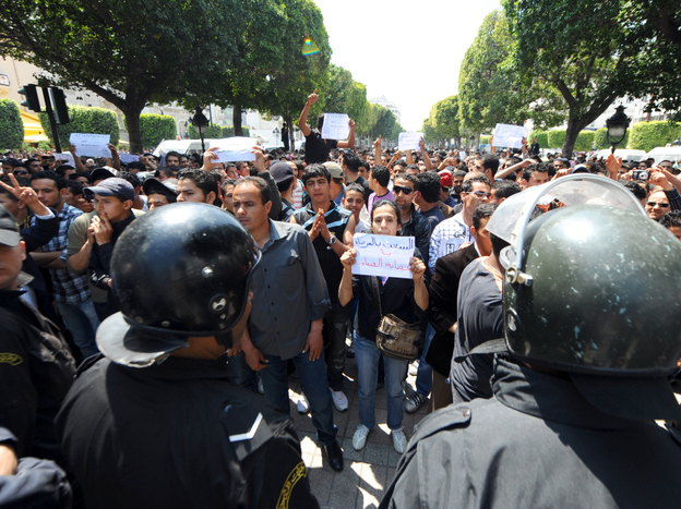 "Tunisian riot police face protestors in the center of Tunis on May 6 during a demonstration organized by youths denouncing the transitional government and calling for ""a new revolution."""