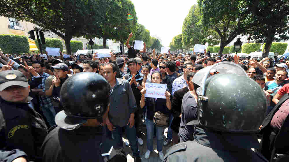 """Tunisian riot police face protestors in the center of Tunis on May 6 during a demonstration organized by youths denouncing the transitional government and calling for """"a new revolution."""""""