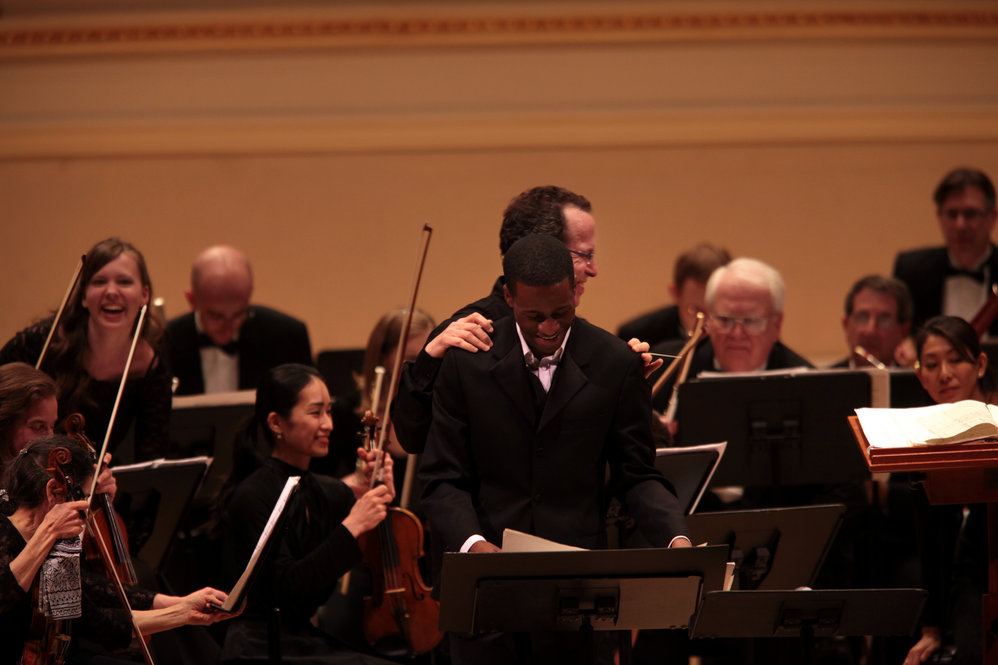 """Baritone Nathan De'Shon Myers is congratulated by music director David Alan Miller after receiving a standing ovation for his performance of """"The Spirituals Project"""" with the Albany Symphony."""