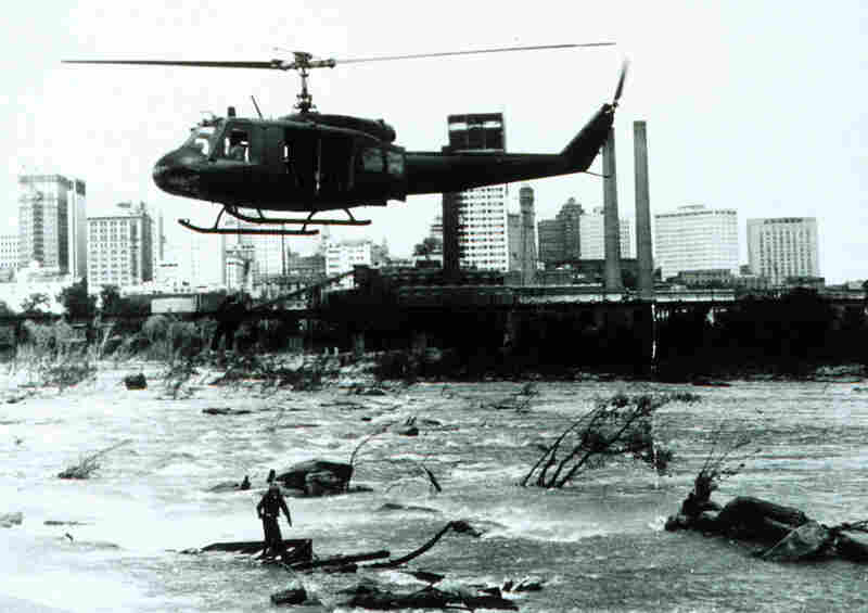A Virginia National Guard crewman stands on debris in the James River as a flood victim is lifted to safety. The 1973 flood affected 16 states, from Illinois to Louisiana, and cost hundreds of millions of dollars in damage.