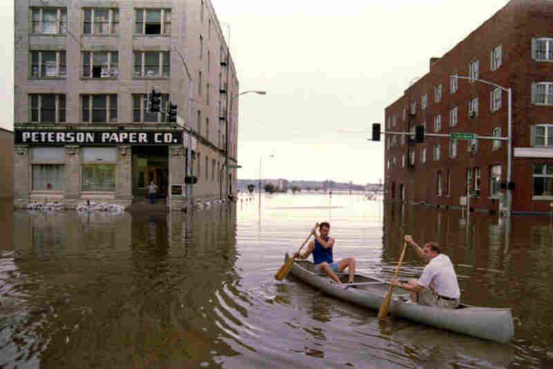 Major flooding in 1993 forced Peterson Paper Co. employee Rick Weber (left) and owner Pete Peterson canoe to work in Davenport, Iowa.