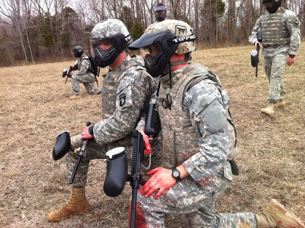 Soldiers with traumatic brain injury clear improvised explosives on a mock mission while taking fire from pretend insurgents armed with paintball guns.