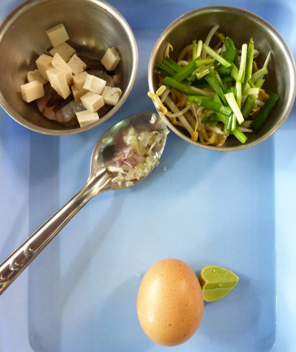 Ingredients for making Pad Thai (Thai Fried Noodles) include diced tofu and spring onions, crushed garlic, egg and lime.