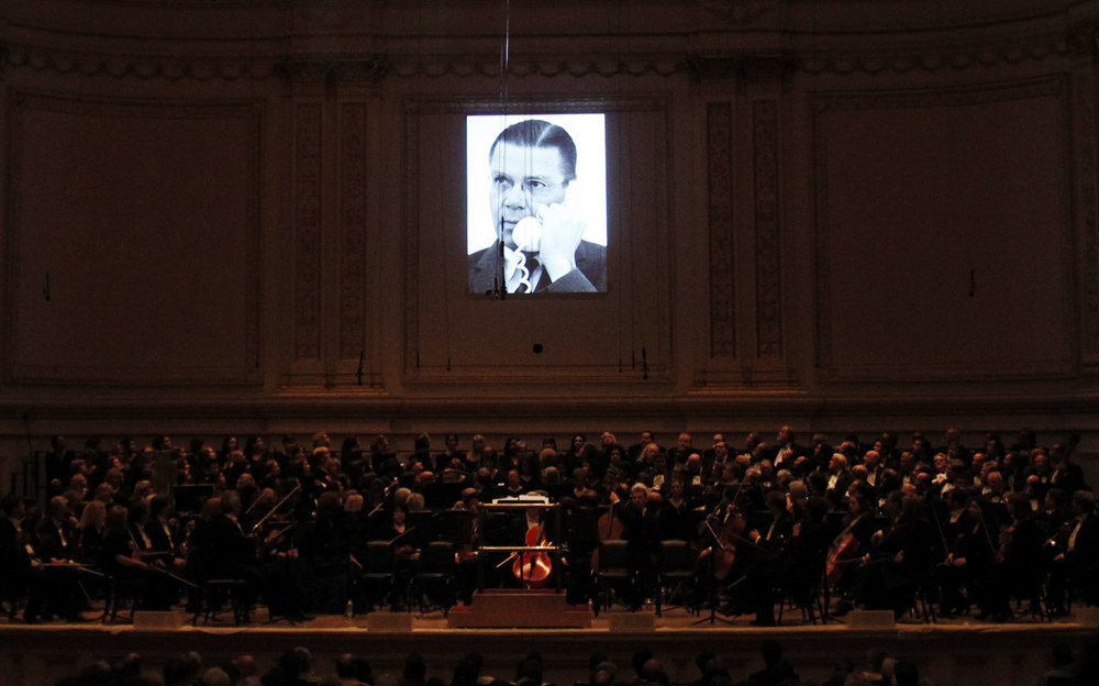 A short film displaying a picture of U.S. Secretary of Defense Robert McNamara is projected above members of the Dallas Symphony Orchestra during the performance.