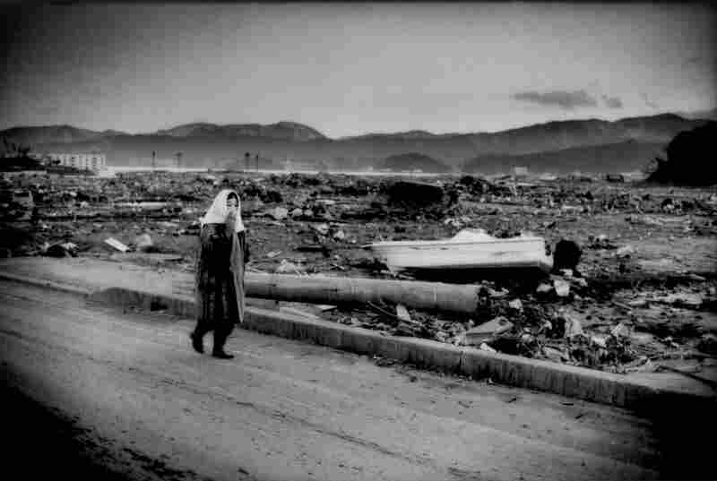 An elderly woman shuffles through a city demolished by the tsunami that arrived 30 minutes after the largest earthquake in Japan's recorded history, Rikuzentakata, Iwate prefecture.