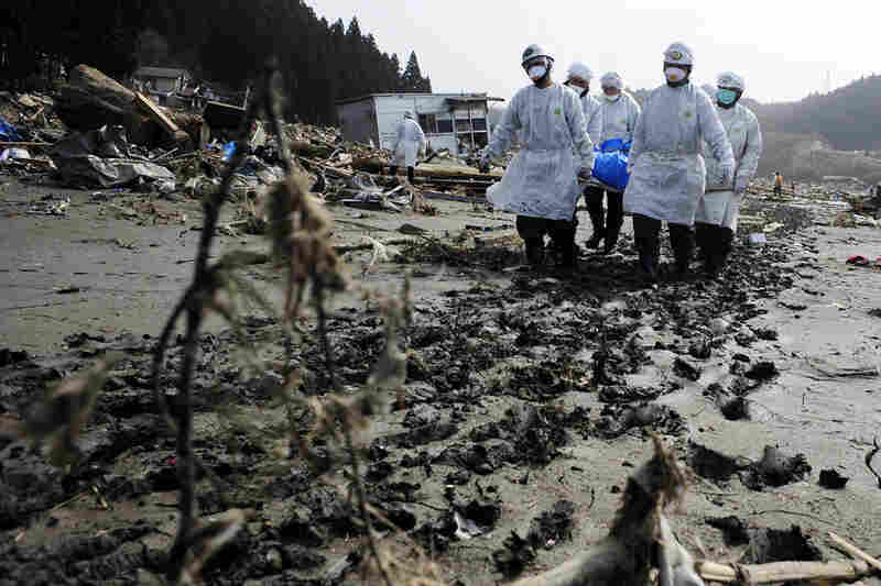 Rescue workers remove bodies in Rikuzentakata, Iwate prefecture, more than a week after the earthquake.