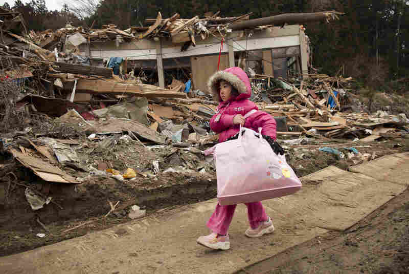 Neena Sasaki, 5, carries some of the family belongings from her destroyed home after the devastating earthquake and tsunami in Rikuzentakata, Miyagi prefecture, March 15.