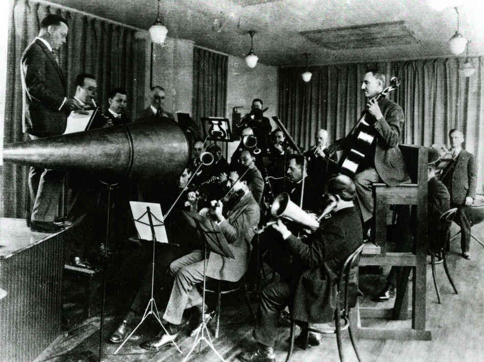 The Victor Orchestra crowds around an enormous horn for an early acoustical recording session.