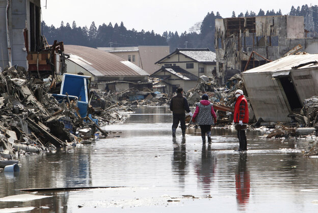 People search for the wreckage of their home washed away by the tsunami at Kesennuma, Miyagi prefecture, March 23, 2011.
