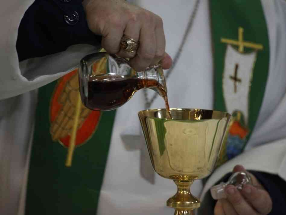 Sept. 2010 file photo: A chaplain pours wine in preparation for communion during a Sunday church service aboard the USS Kearsarge.