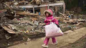 Neena Sasaki, 5, carries some of the family belongings from her home that was destroyed after the earthquake and tsunami in Rikuzentakata,  Miyagi province, Japan, March 15, 2011.