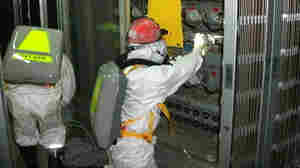 A worker checks the status of the water level at the Unit 1 reactor at the Fukushima Dai-ichi nuclear power plant in Japan on Tuesday. Japanese officials said the reactor doesn't appear to be holding water, which means its core probably sustained more damage than originally thought.