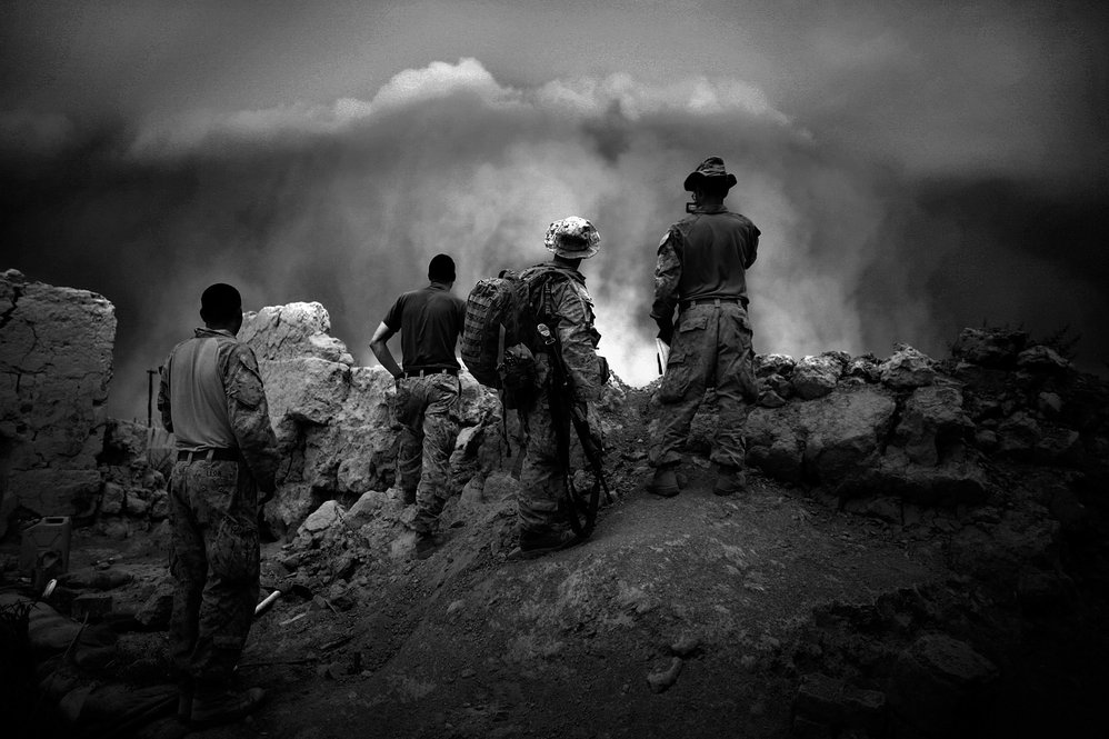 Marines watch as a massive dust storm approaches their base. Though fighting slows during poppy harvest, Marines remain on edge, as fighting could erupt at any moment.