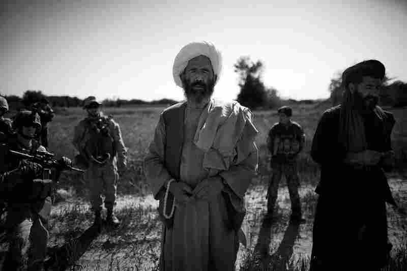 """A local farmer talks with Marines in the """"green zone"""" — a strip of irrigated land along the main Helmand River, also a hotbed for insurgency and violent fighting after poppy cultivation ends."""