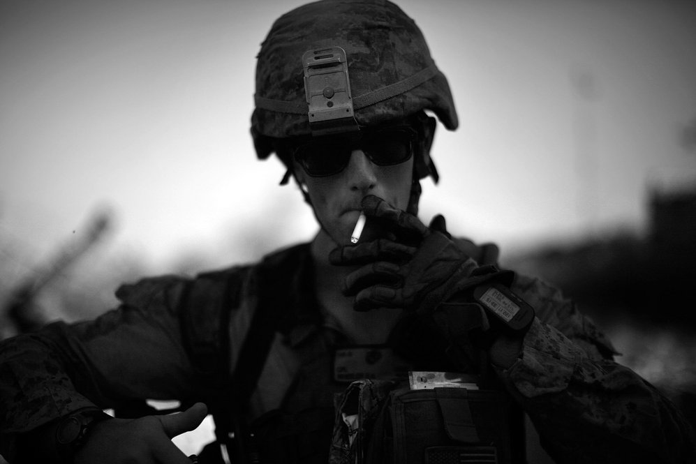 "Cpl. Daniel Wheeler lights a cigarette after late afternoon patrol in the scorching heat. Some of the Marines have nicknamed the area ""Vietnamistan,"" after the marshes and junglelike terrain that they navigate daily."