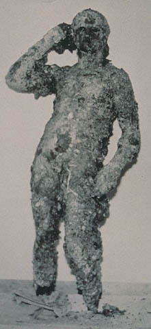 The Getty Bronze, covered in barnacles, as it appeared in 1964, when it was pulled out of the sea by fishermen off the coast of Fano, Italy.
