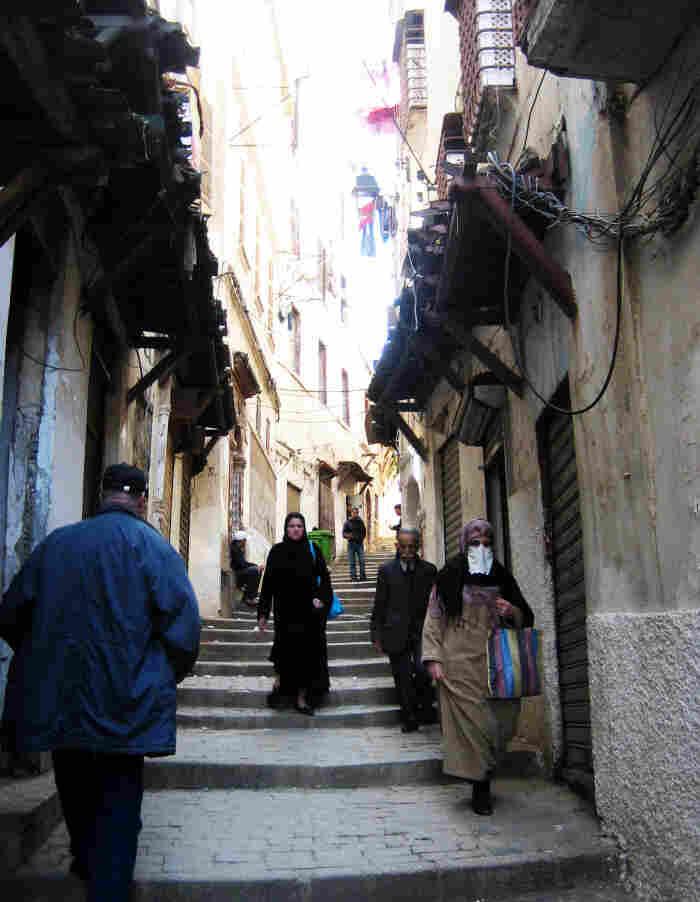 Women walk down a winding street in the Casbah in Algiers.