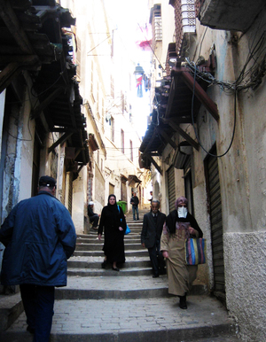Women walk down a winding street in the Casbah in Algiers.