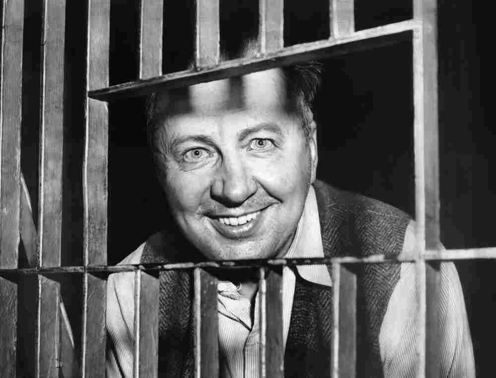 """George Metesky, who confessed to being the """"Mad Bomber,"""" looks through the bars of his cell at the Waterbury, Conn., Police Station."""