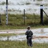 A member of the Louisiana National Guard stands guard as water diverted through the Morganza Spillway begins to fill a pasture in Morganza, La., on Saturday.