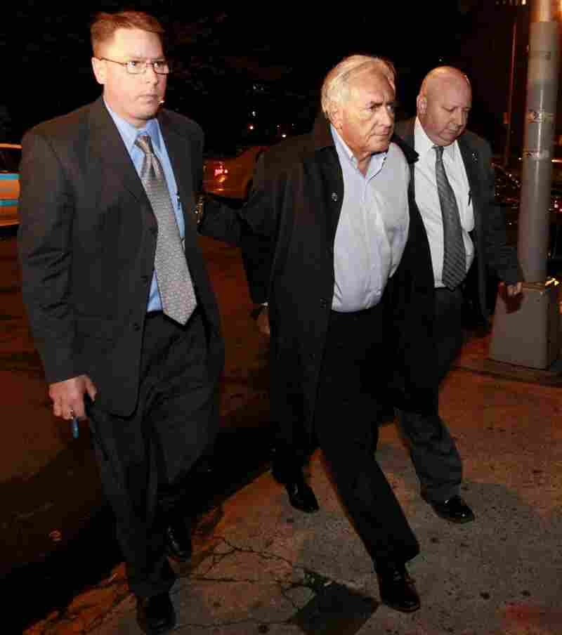 International Monetary Fund leader Dominique Strauss-Kahn (center) is led into court early Monday in New York.