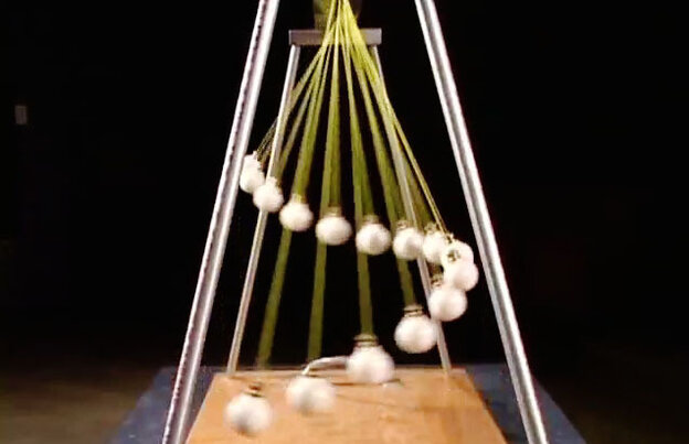 A still frame from a video of pendulums dancing together creating waves.