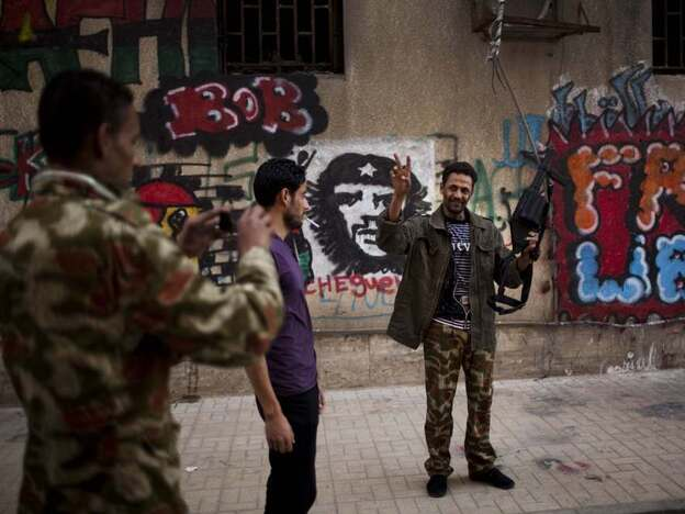 A rebel soldier takes a picture of a comrade on May 5 outside the National Council, the headquarters of the rebels in Benghazi, Libya. The rebel-led transitional government is seeking legitimacy and recognition from the international community.