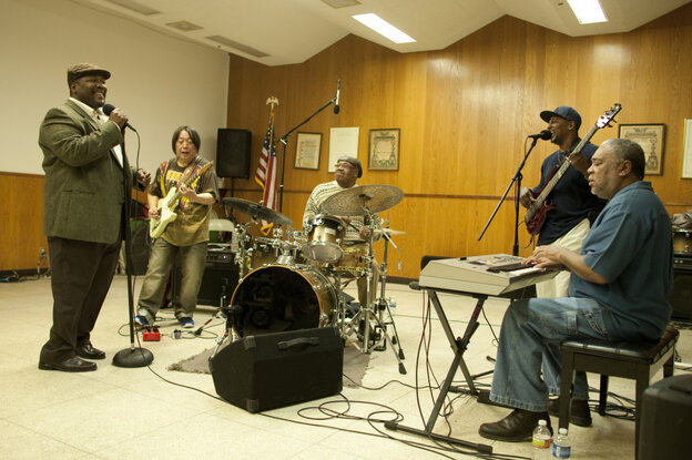 Antoine Batiste (Wendell Pierce, left) leads a rehearsal with his Soul Apostles, featuring guitarist June Yamagishi.