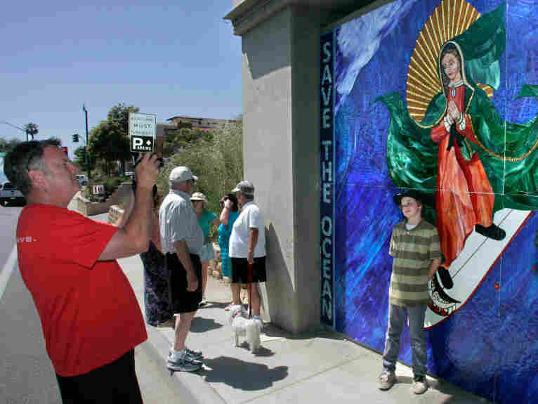 San Diego resident Brennan Savage  photographs his son, Liam, posing with the Madonna-surfing mosaic on Encinitas Boulevard's railroad bridge support.