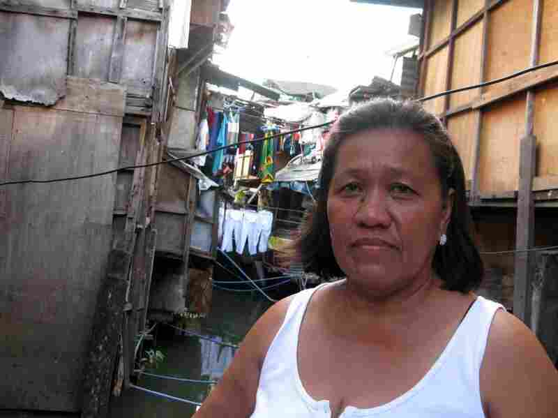 Community organizer Filomena Cinco stands amid shacks on the Estero de San Miguel, a slum neighborhood in Manila. Residents want to redevelop their neighborhood, rather than be relocated to distant suburbs under a government plan.