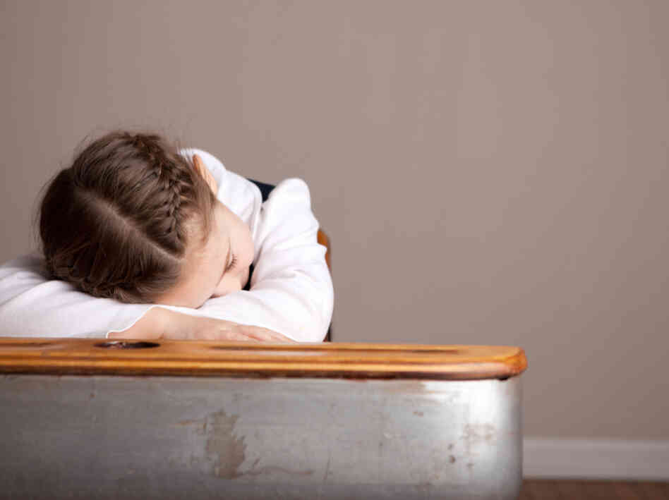 A sleepy girl snoozes at her school desk.