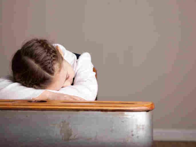 A sleepy girl snoozes at her school desk.