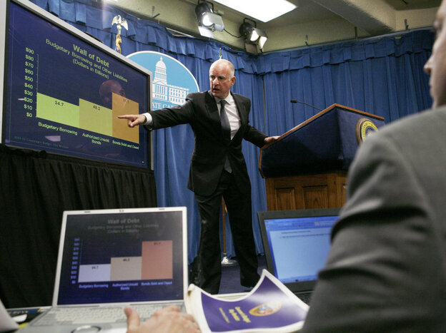 Gov. Jerry Brown points to a chart at a news conference at the Capitol in Sacramento, Calif.