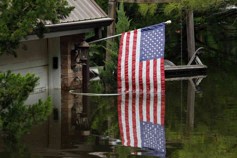MAY 20: An American flag reflects in Mississippi River floodwaters outside of a home in south Vicksburg, Miss.