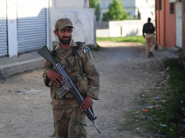 Pakistani military and police officials cordoned off a street in Abbottabad near the compound where Osama Bin Laden was found and killed. (May 8, 2011, file photo.)