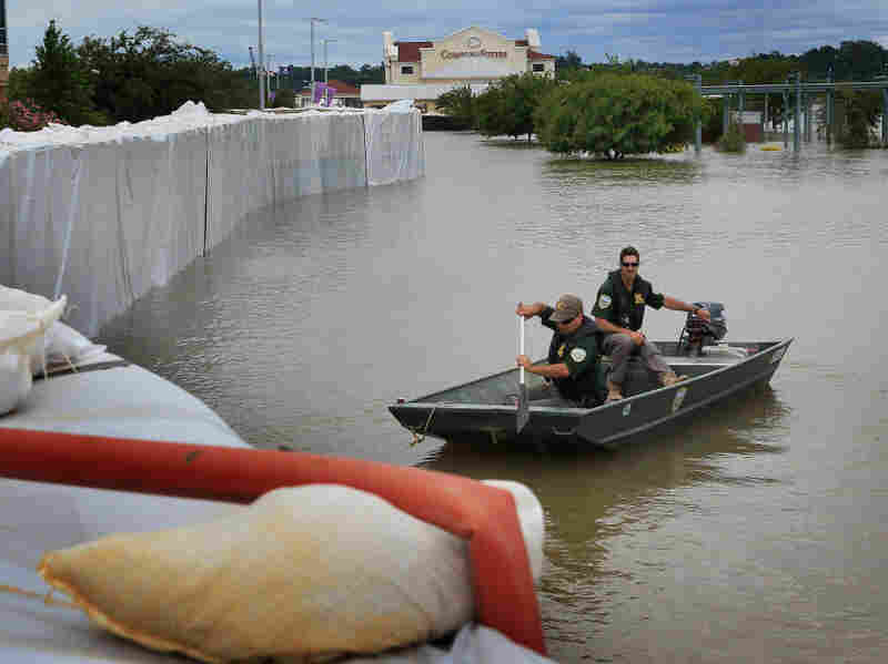 Louisiana Department of Wildlife and Fisheries officers patrol along a  levee constructed around a medical center to hold back floodwater from  the Mississippi River on Monday in Vidalia, La.