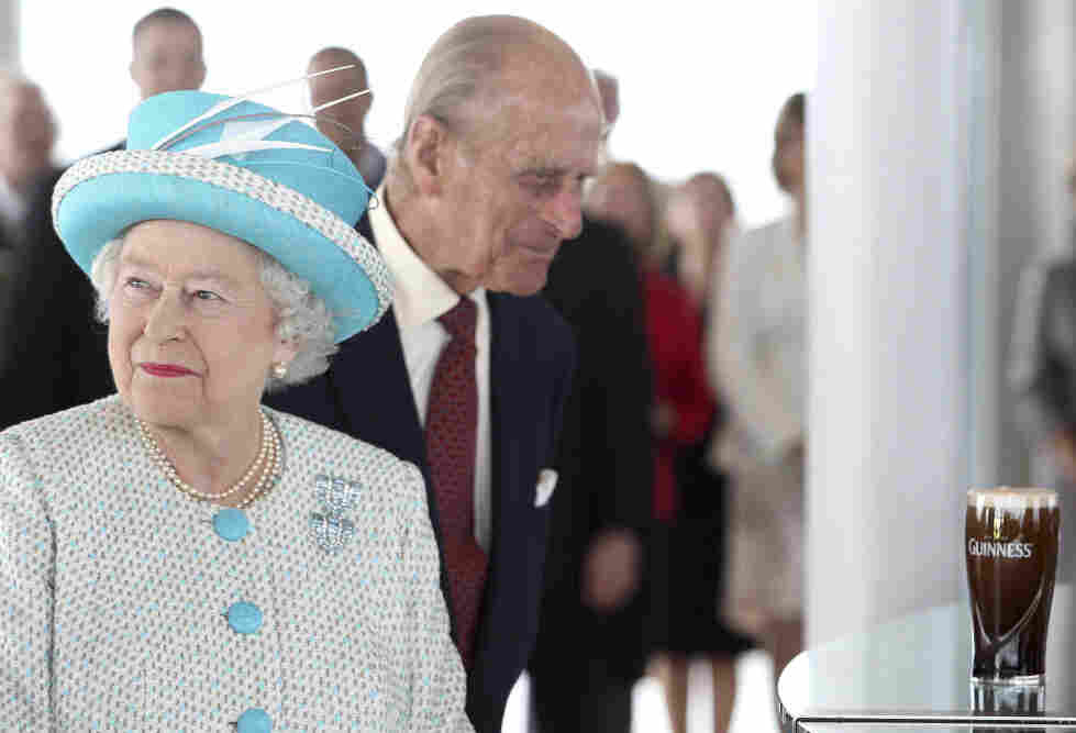 As Queen Elizabeth II looks away, Prince Philip eyes the pint of Guinness poured for them today (May 18, 2011) in Dublin. Neither took a sip.