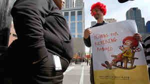 During a demonstration in Chicago, Jack Nugent (right), part of a group organized by Corporate Accountability International, urged a pedestrian to support his cause calling for McDonald's to retire Ronald McDonald in March 2010.