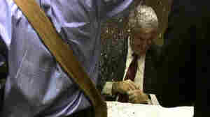 A protester literally turns Newt Gingrich into a glitterati member at a Minneapolis book signing, May 17, 2011.