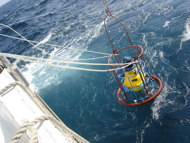 Geologists drop an acoustic transponder into the Pacific Ocean to measure movements on the seafloor.
