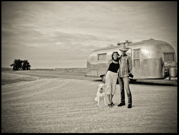 David Michael Kennedy with Heather Howard and Henry Crow Dog in front of their 1959 Airstream trailer.
