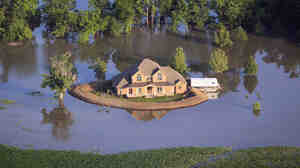 A levee protects a home surrounded by floodwater from the Yazoo River near Vicksburg, Miss., May 18, 2011.