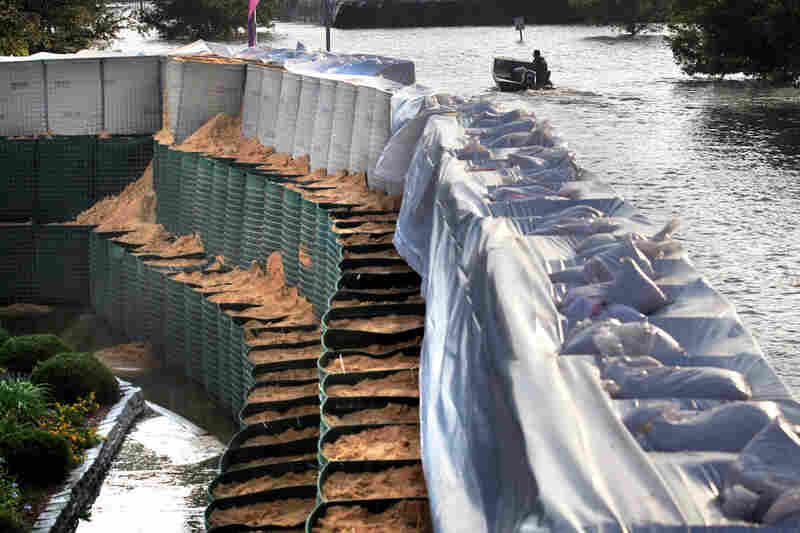 MAY 19: A boat motors through Mississippi River floodwaters past a wall of flood-containment baskets, known as Hesco baskets, that is protecting the Riverside Medical Center in Vidalia, La.