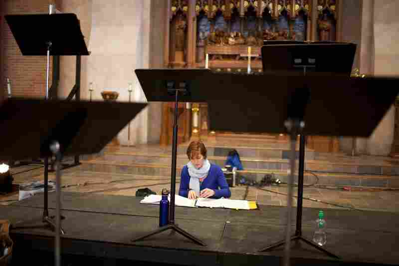 Dorea Cook, who sings alto with Conspirare, looks over her sheet music during a break from rehearsal.