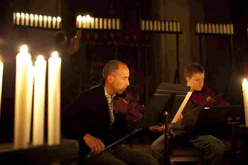 Musicians Greg Luce (left) and Stephen Redfield run through their music, as stagehands light candles in preparation for a dress rehearsal.