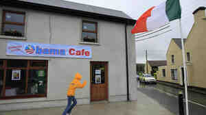 A youngster runs past the soon-to-open Obama Cafe in Moneygall, Ireland, on Saturday. President Obama is due to visit the village, the ancestral homeland of his great-great-great grandfather, as part of his 24-hour visit to Ireland on Monday.
